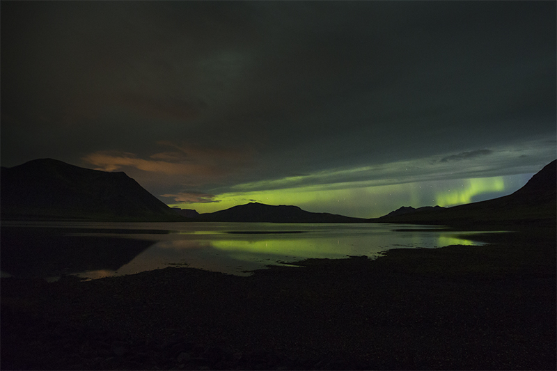 Aurora between clouds and mountains in Seljafjordur at Snæfellsnes