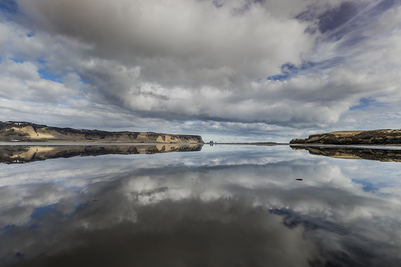 Two Pillars at black beach and its reflection