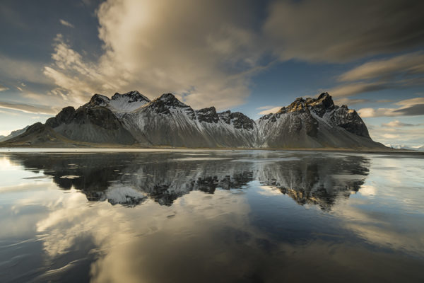 Majestic mountain Vestrahorn and its reflection in the wet beach sand