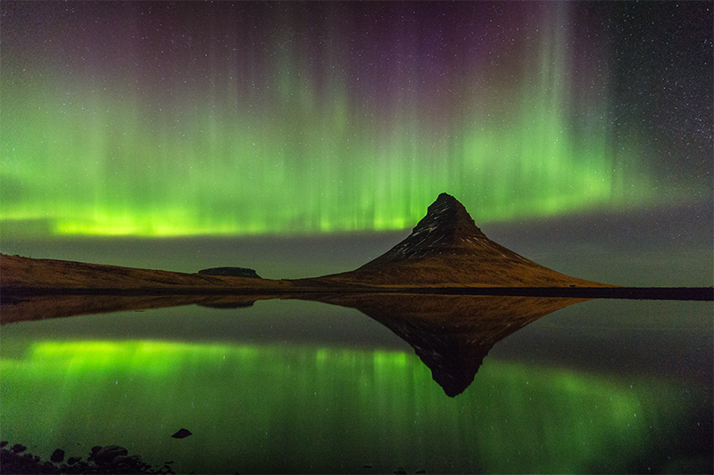 The majestic mountain Kirkjufell and Aurora reflection