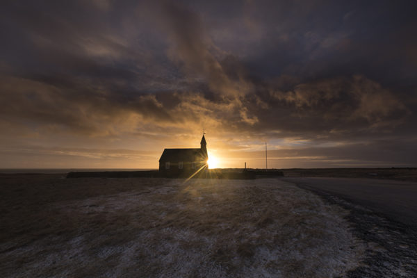 Sunrise at black church in Búðir
